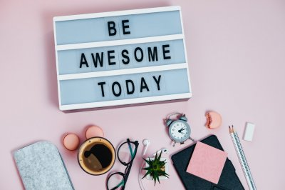 Board be awesome today on pink glasses notepad kicking pencils plant macaroons alarm clock Top View Flat Lay